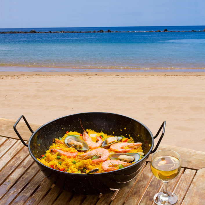 Seafood paella with glass of wine in seaside cafe